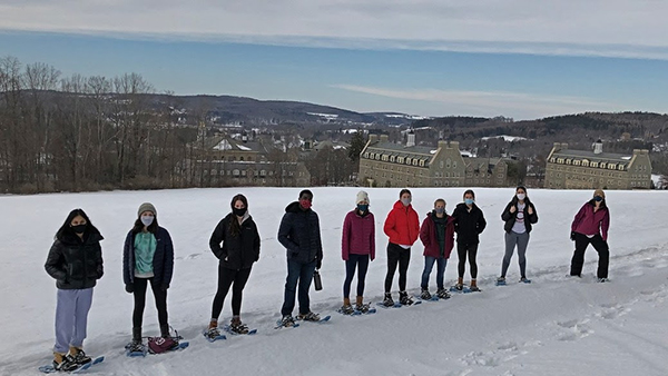 Group of students snowshoeing with professor