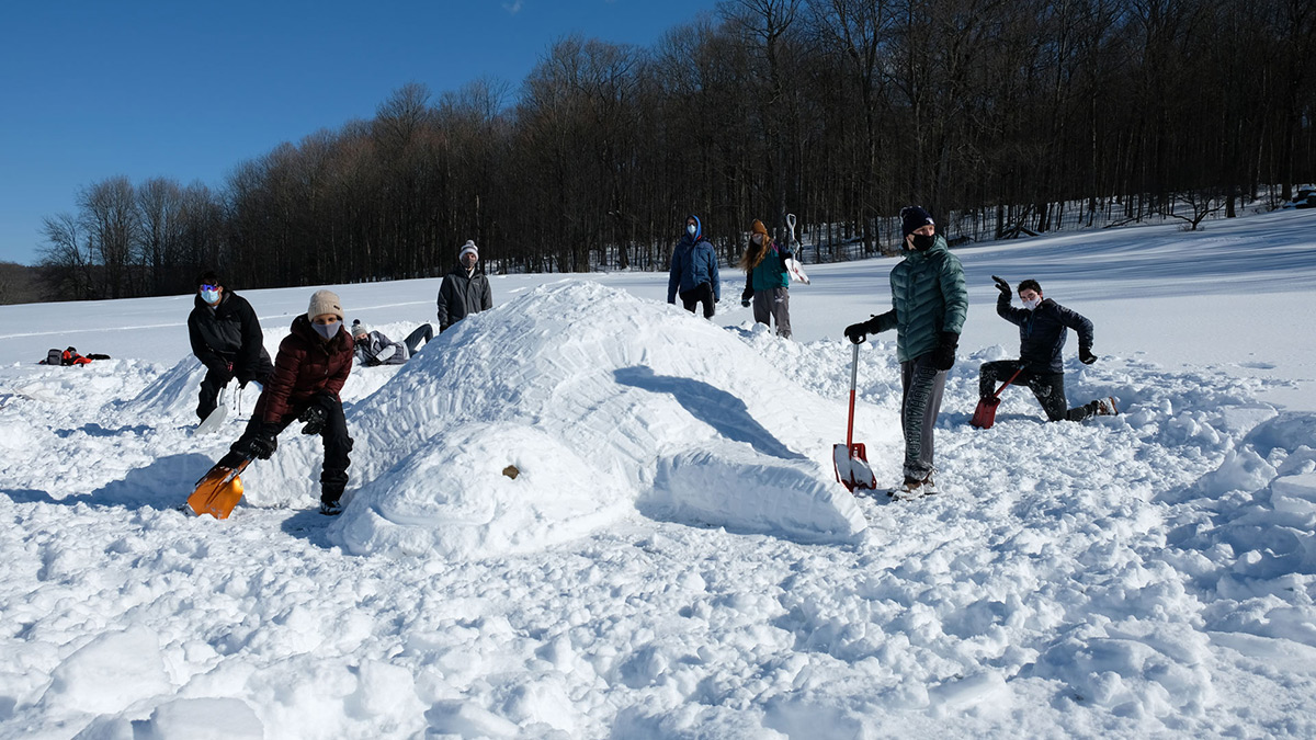 Students with snow sculpture shaped like a turtle